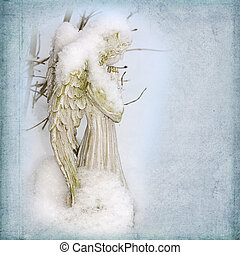Snow Angel - Angel statue covered in snow in a soft blue...