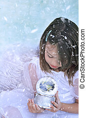 Little angel in the snow holds a snow globe and watches the earth. Elements of this image furnished by NASA.""