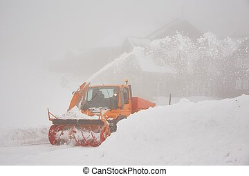 Snow blower is working on the road in mountains
