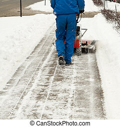 Snow blower - Man working with a snow blowing machine