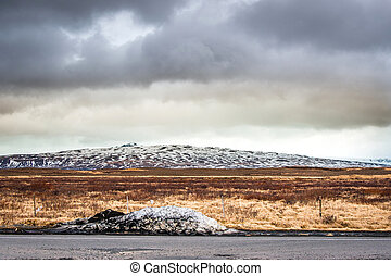 Snow by a road in dramatic scenery