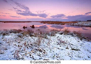 snow by lake at sunrise