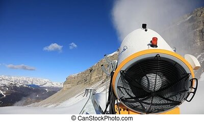 Snow cannon against the blue sky. Snow-making is the...