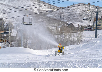Snow cannon and ski lifts on sunlit snowy slope. Snow canon...