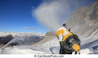 Snow cannon at work - Yellow snow cannon stands on a snowy...