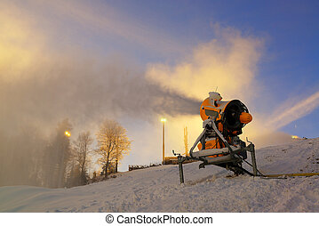 Snow cannon prepares ski slope early in the morning. Winter...