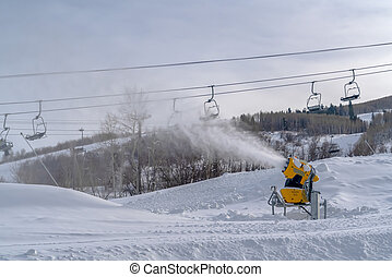 Snow canon and chair lifts on snowy mountain. Yellow snow...