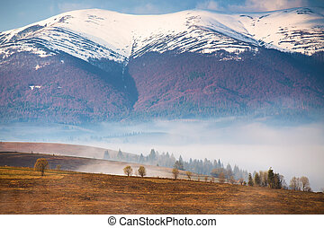 Snow caped mountains. Morning fog in valley. Misty hills