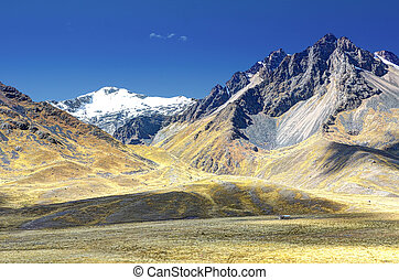 snow capped Andes mountains and rolling hillsides in Peru