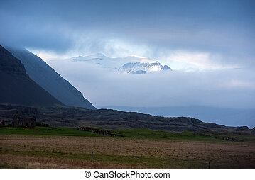 Snow capped mountain and clouds in Iceland