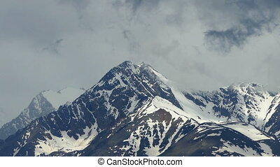 snow-capped mountain peaks among the clouds