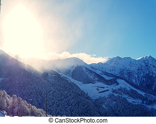 Snow-capped mountain valley against the backdrop of blue sky and bright sunlight