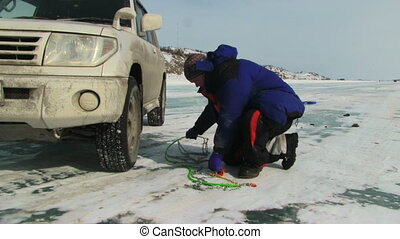 Snow Chains - Men putting snow chains on tire
