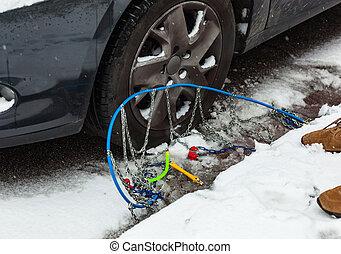Snow chains near the car tire.