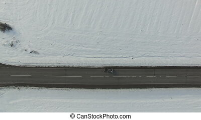 Snow clearing mashine clears a road in snowed winter field...