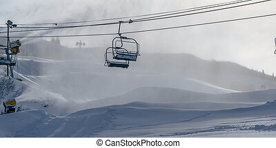 Snow cloaked mountain with ski lifts and snow guns. Park...