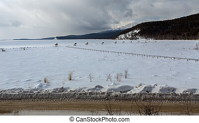 Snow-covered arbors on the shore of winter lake Baikal