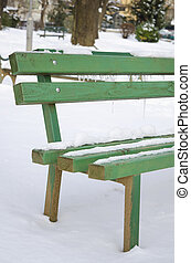 Snow covered bench in a park