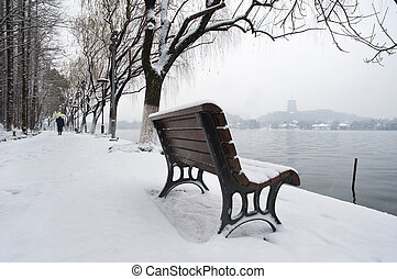 Snow-covered bench on the banks of West Lake, Hangzhou,...