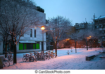 snow covered bicycles on the street