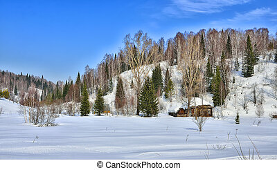 Snow covered cabin in the mountains valley
