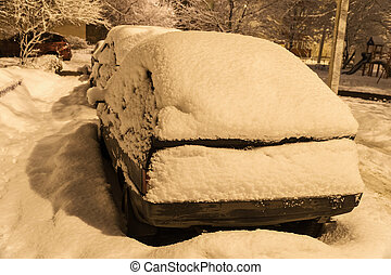 Snow-covered car in the evening