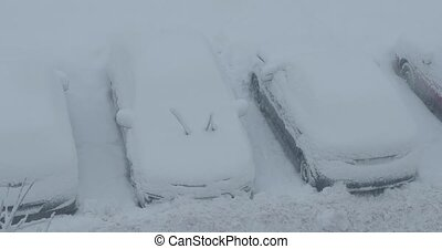 snow covered cars in the parking lot.