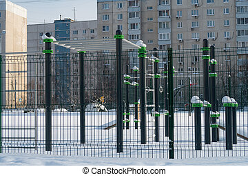 Snow-covered complex of sports simulators in the courtyard of a school in a residential area of the Moscow region