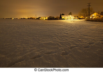Snow Covered Field And Christmassy Village - View over a...