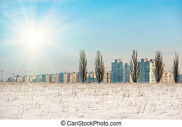 Snow-covered field with dry grass and distant city