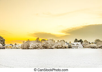 snow covered fields with settlement at the horizon in...