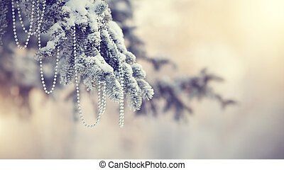 Snow-covered fir-tree branch with Christmas-tree decoration