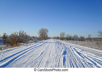 Snow covered forest country road on winter sunny day