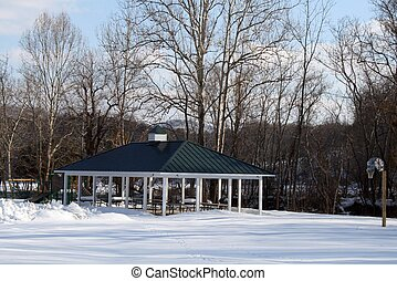 Snow covered gazebo in park - a snow covered park shown...