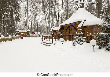 Snow-covered house in beautiful winter forest - Snow-covered...