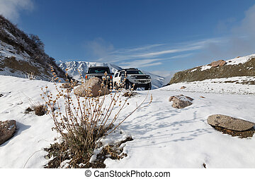 Snow-covered mountain pass with two SUV