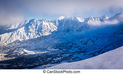 Snow covered mountain valley at sunrise