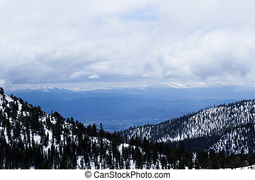 Snow Covered Mountains With Trees And Clouds