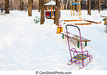 snow-covered playground in urban park in winter
