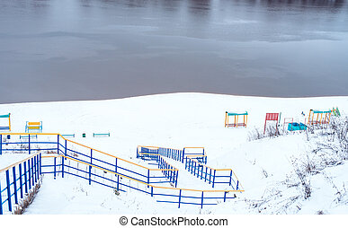 Snow-covered playground on river bank in winter. Snowy hills next to the river ridge to the river.