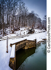 Snow covered railroad bridge over a creek in rural Carroll County, Maryland.