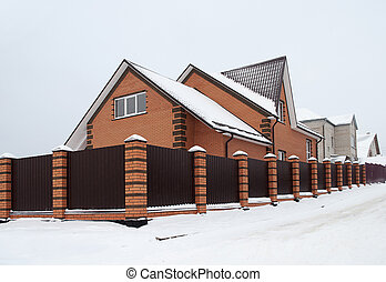 Snow covered red brick house with metal fence - Snowbound ...