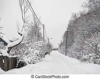 Snow-covered road. A lot of snow in the village.