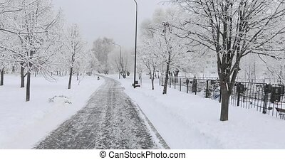 Snow-covered road along the cemetery