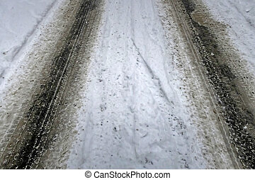 Snow covered road and car tire tracks in winter