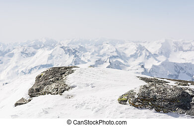 Snow covered rock with a mountain view in the back