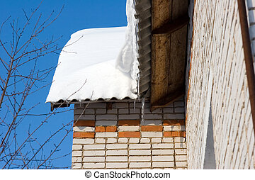 Snow covered roof with icicles