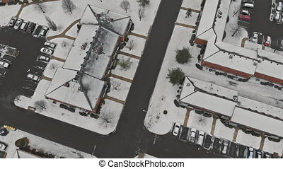 Snow covered rooftops and street in winter aerial view of ...