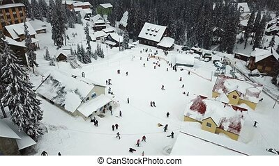 Snow-covered ski resort in the mountains with Christmas trees