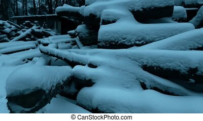 Snow covered timber supply at sawmill. Steadicam shot - Snow...